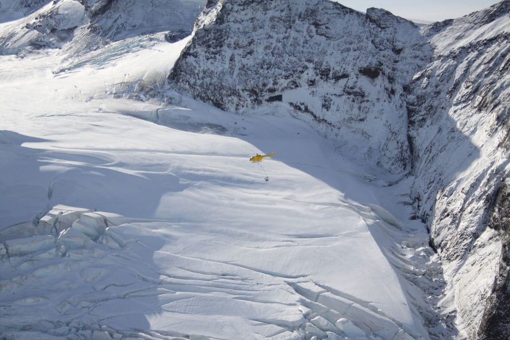 Helicopter transporting rat bait across the frozen mountains on South Georgia Island.