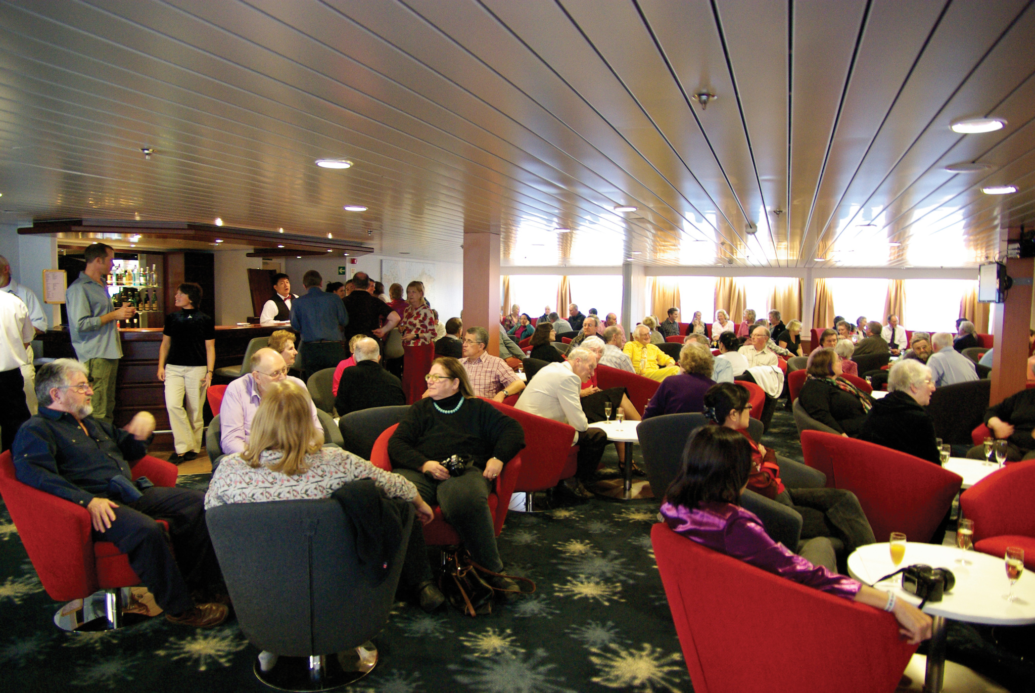 people enjoying a drink and chat in the bar on an antarctic cruise vessel.
