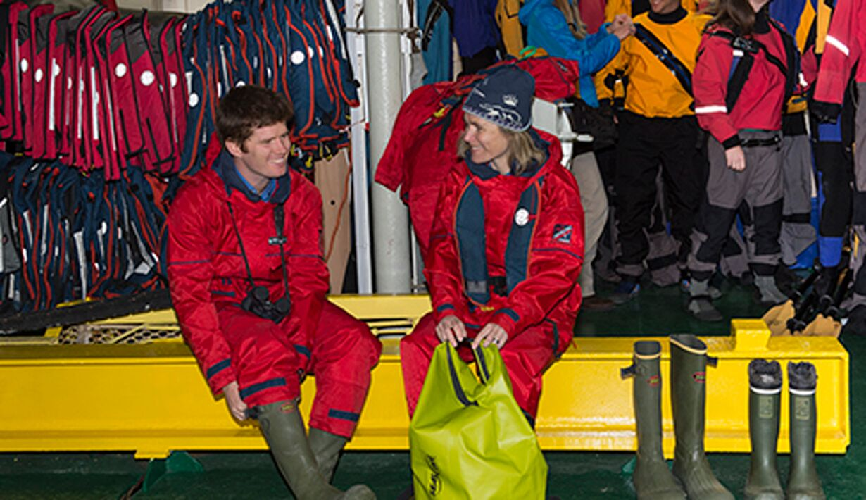 Pulling rubber waterproof boots on before boarding a zodiac from a polar cruise ship
